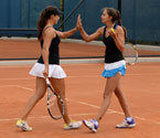 Ipek Soylu and Muge Topsel high-fiving each other after winning a crucial point during the girls doubles final